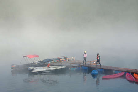 Foggy landscape with calm lake and pier.Mist over water. Beautiful freedom moment and peaceful atmosphere in nature.