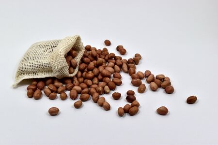 goober: Peanuts in the cloth bags on white background.