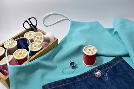 singlet: Blue lady singlet,Jeans and sewing equipment. Stock Photo