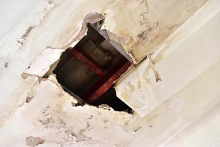 Regenwater lekt op het plafond en veroorzaakt schade, tegels en gipsplaat. Stockfoto
