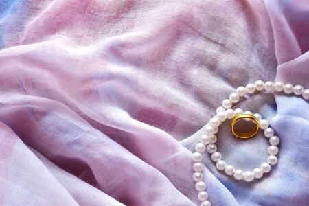 Top view gold ring and pearl necklace on the pink fabric , Empty space for text.
