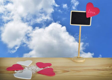 A small heart shaped label on a wooden table  , clipping path included to remove the background with ease.