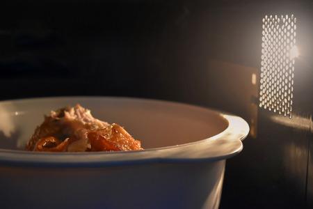 Kijk in de magnetron voedsel witte kom, in een warme sfeer en lege bovenste ruimte voor tekst.