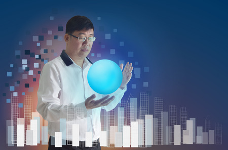 The business man asians wear glasses. Stand and use the hand to hold the shiny ball ,  On a blue background concepts of communication  and empty space for text. Stock Photo