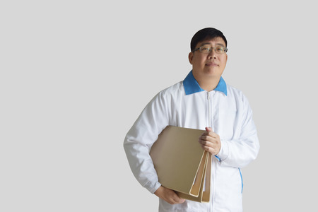 Asian man aged 40 to white long-sleeved shirt uniform . holding a brown file On background of gray with clipping path and empty space for text.
