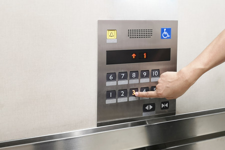Men's hand with the press of control buttons interior elevator have braille panel for the disabled and empty space for text . 版權商用圖片