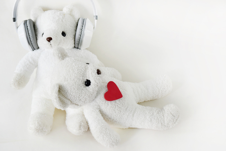 White teddy bear wearing headphones and sleeping on the lap.The day of love and the day of music.