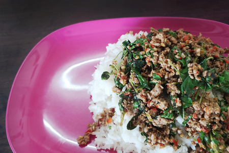 Fried rice with basil in a plastic pink plate on a wooden table,Concept Spicy foods that should not be used in certain types of containers.