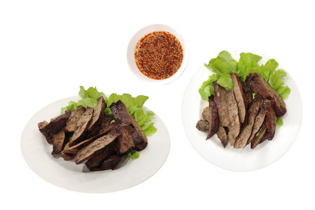 Grilled pork liver in a white dish and spicy flavor, isolated on white background with clipping path.Traditional Asian Food.