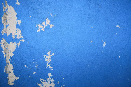 Rain water leaks on the ceiling causing damage, peeling paint and moldy. blue wall texture and empty space for text.