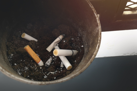Many types of cigarette butts are left in the ashtray and empty rightspace for text .