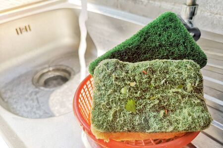 Scrub sponge for cleaning kitchen utensils and various surfaces On the sink.