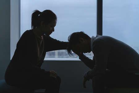PTSD concetto di salute mentale, giovane uomo asiatico depresso che parla con lo psicologo seduto vicino alla finestra in una stanza buia alla sera con un ambiente poco luminoso. Messa a fuoco selettiva.