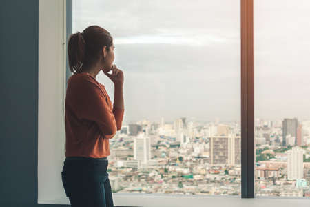 Young depressed asian woman standing alone near window in dark at evening time with low light environment, PTSD Mental health concept, Selective focus.