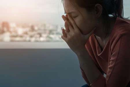 Young depressed asian woman sitting alone near window in dark at evening time with low light environment, PTSD Mental health concept, Selective focus.