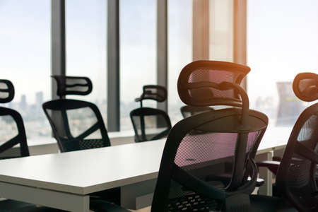 Close up of table in meeting room with large windows and city tower view with blur sky, Selective focus.