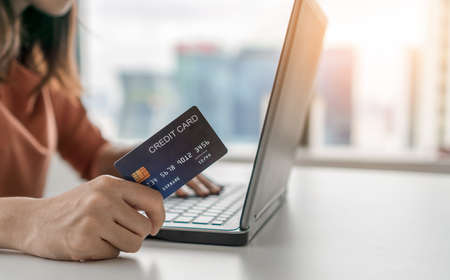 Young asian woman holding credit card and use laptop for purchase product on internet in home office, Cyber Monday shopping online concept. Reklamní fotografie