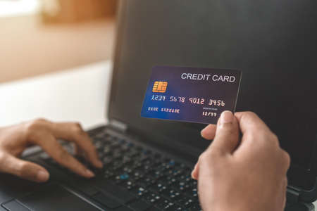 Close up of young asian woman hand holding credit card and use laptop for purchase product on internet in home office, Cyber Monday shopping online concept.