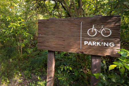 Wooden sign of a bicycle parking  green on forest background. copy space for adjust your text or message. Reklamní fotografie
