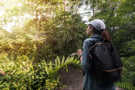 Summer journey vacations concept, Asian woman traveler with backpack standing near tropical forest and looking far away.