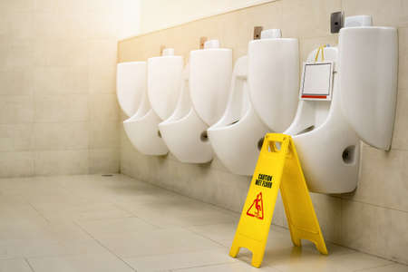 Out of service of Urinal pot with yellow sign warning caution wet floor or cleaning in progress in toilet.