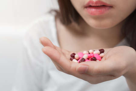 Close up hand of young asian woman taking medicine overdose trying to kill herself, Sick woman take a lot of pills, Suicide prevention concept. Reklamní fotografie