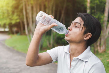 Exercise and healthy concept, Young asian man runner relaxing drinking water in bottle in the park outdoors after sport at early morning time.