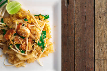 Top view overhead photo, Traditional thai food, Shrimp Pad Thai noodle on white dish, with copy space Reklamní fotografie