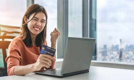 Young asian woman holding credit card and use laptop for purchase product on internet in home office, Cyber Monday shopping online concept, Copy space.
