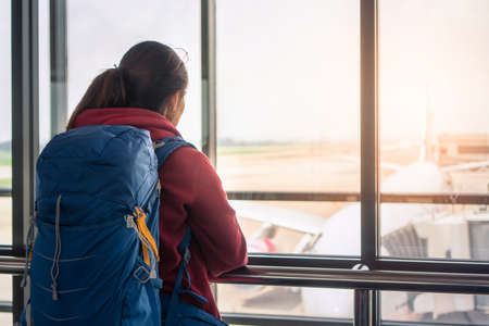 Traveler asian woman standing at the window in hall airplane departure with backpack , Selective focus, Travel concept.