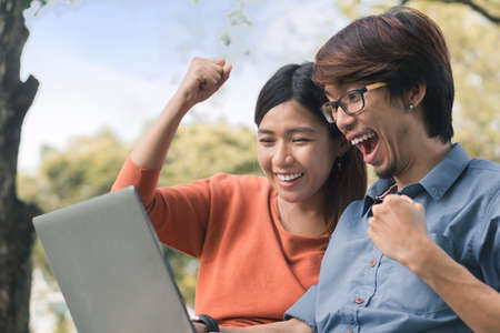 Couple young asian man and woman working with laptop and enjoying cheerful his online winner success  on a bench in the park outdoors on vacation time.