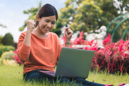 Happy young asian woman working with her laptop and enjoying his online winner success  in the park outdoors on vacation time. Reklamní fotografie