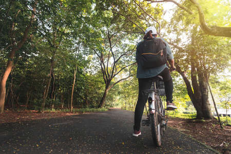 Summer travel concept, Young asian woman wear jean shirt riding bicycle on forest trail at morning tropical in her vacation.