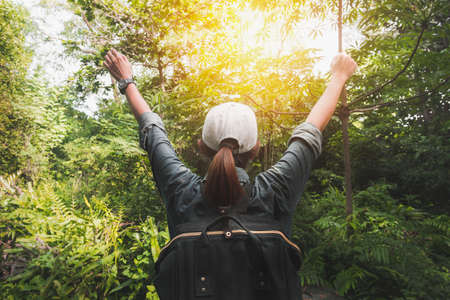 Summer journey vacations concept, Asian woman traveler with backpack standing and hand up near tropical forest and looking far away.
