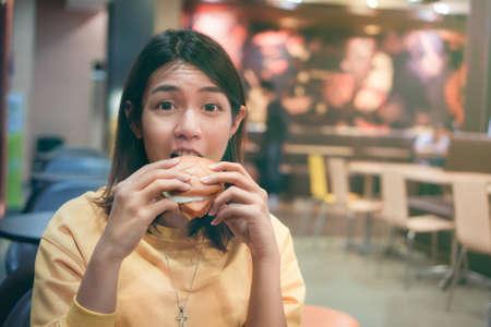 Young asian woman eating hamburger in fast food store. fatty junk food hamburger.