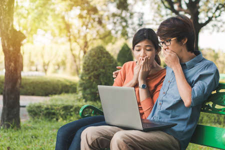 Couple young asian man and woman working with laptop and surprise enjoying cheerful his online winner success  on a bench in the park outdoors on vacation time.