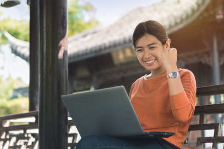 Young asian business woman working with his laptop and enjoying his online winner success on a bench in the park outdoors on vacation time. Reklamní fotografie