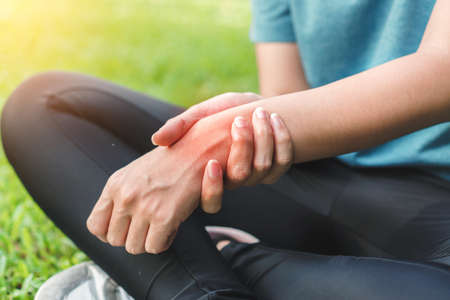 Young woman asian have accident and holding her wrist pain twist sprain in sport exercise jogging, selective focus.