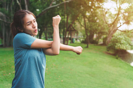 Exercise and healthy concept, Young asian woman runner stretching arm before running at morning, selective focus