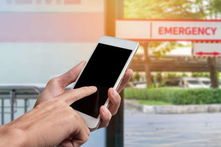 Close up of hand holding smartphone with blank black screen(with clipping path for adjust you text) on emergency room in hospital background.