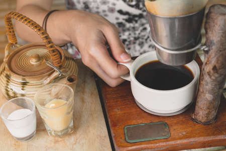 Happy asian woman holding a cup of drip coffee on wooden table,Enjoying morning coffee concept.