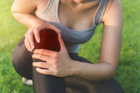 Exercise and healthy concept, Young woman asian have accident knee twist sprain in sport exercise jogging, Selective focus