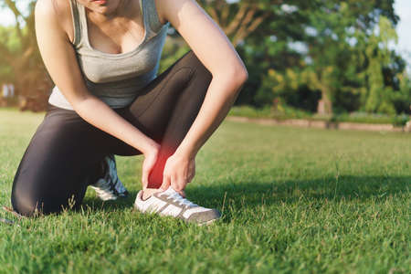 Young woman asian have accident ankle twist sprain in sport exercise jogging, selective focus Reklamní fotografie