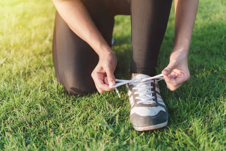 Exercise and healthy concept, young asian woman prepare shoe before running in the morning, selective focus.