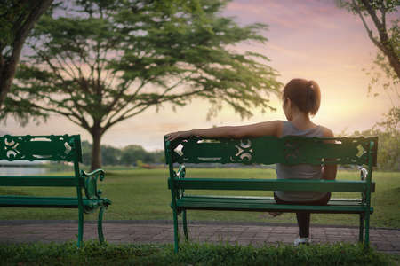 Exercise and healthy concept, Young asian woman runner relaxing  and sitting on bench in the park outdoors after sport at early morning time.
