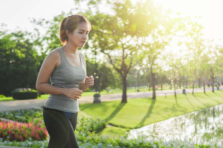 Exercise and healthy concept, Young asian runner woman running in the park in sportswear morning time, selective focus