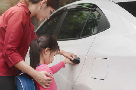Back to school concept, Beautiful young asian mother or parent helping daughter or pupil to getting in the white car to ride to school, Selective focus.