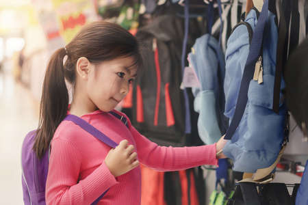 Back to school concept, Young asian girl kid or cute pupil buying school satchel or bag in store, Selective focus