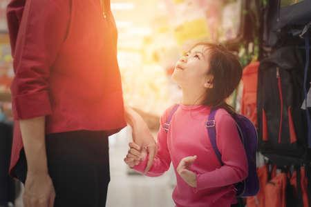 Zurück zum Schulkonzept, junge asiatische Mutter oder Elternteil und kleines Mädchen, das Schulranzen oder Tasche im Laden kauft, Selektiver Fokus