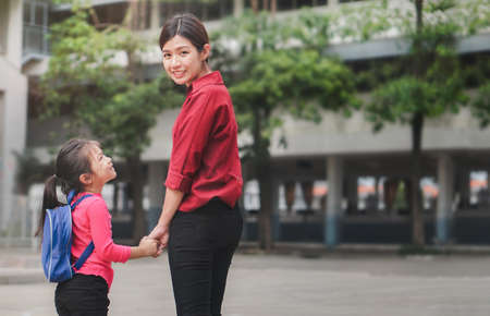 Back to school concept, Mother or parent holding hand  daughter or pupil with backpack to school, Selective focus.